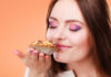 Bakery sweet food and people concept. Content attractive woman closed eyes holds cake cupcake in hand smelling orange background